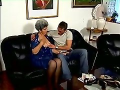 busty white mature lady sucking dick of a young man on the couch