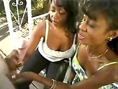 Two Black women giving white man a handjob