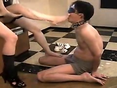 Two dominant girls make a blindfolded slave lick their feet