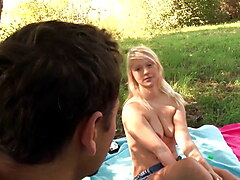 Little blonde girl is surprised in the park while sunbathing